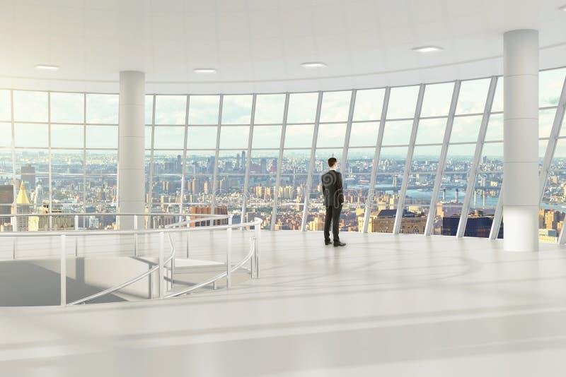 Homem no escritório vazio claro moderno com opinião da cidade imagem de stock royalty free