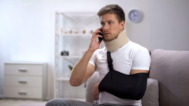 Homem no estilingue do braço e no colar cervical da espuma que fala no telefone celular, virada com notícia foto de stock royalty free