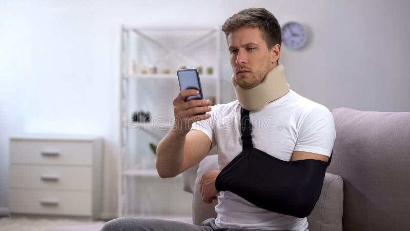 Homem no estilingue do braço e para espumar desdobramento cervical no smartphone, período do colar da reabilitação foto de stock