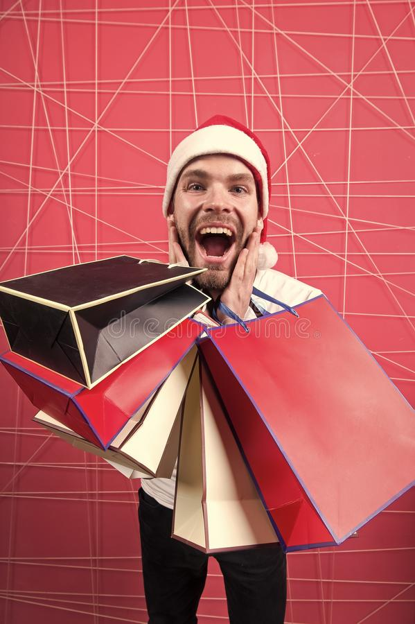 Homem no grito feliz do chapéu do xmas com sacos coloridos imagens de stock royalty free