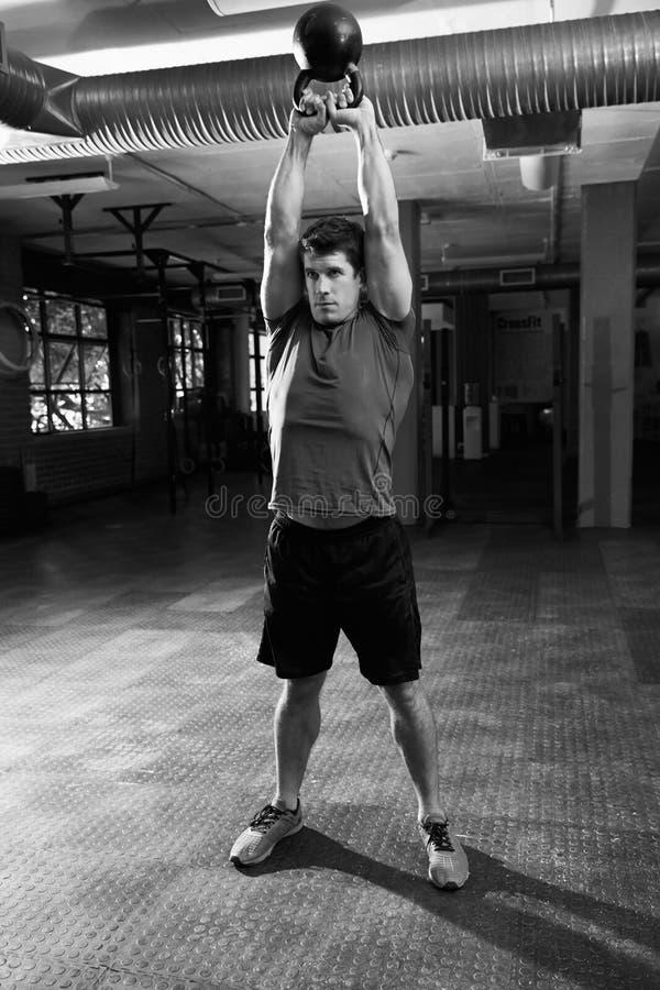 Homem no Gym que exercita com peso de Bell da chaleira imagens de stock royalty free