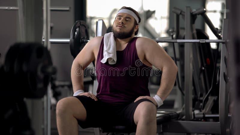 Homem no gym que finge ser atlético, sentando-se como macho, motivação do exercício foto de stock