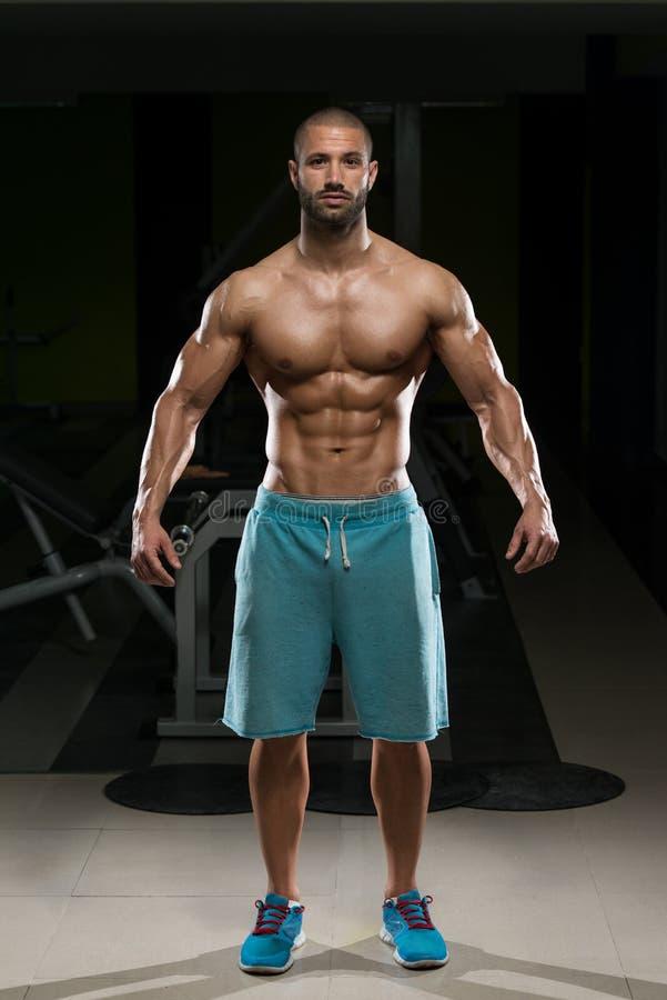 Homem no Gym que mostra seu corpo bem treinado foto de stock