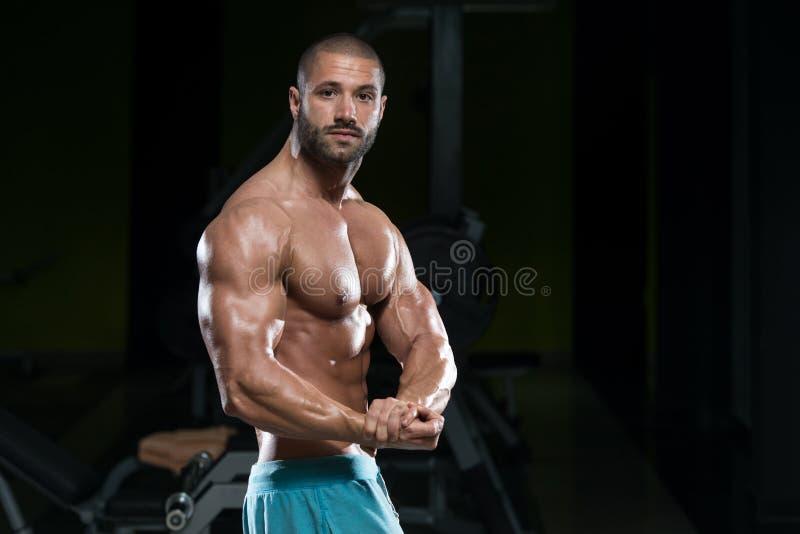 Homem no Gym que mostra seu corpo bem treinado fotografia de stock royalty free