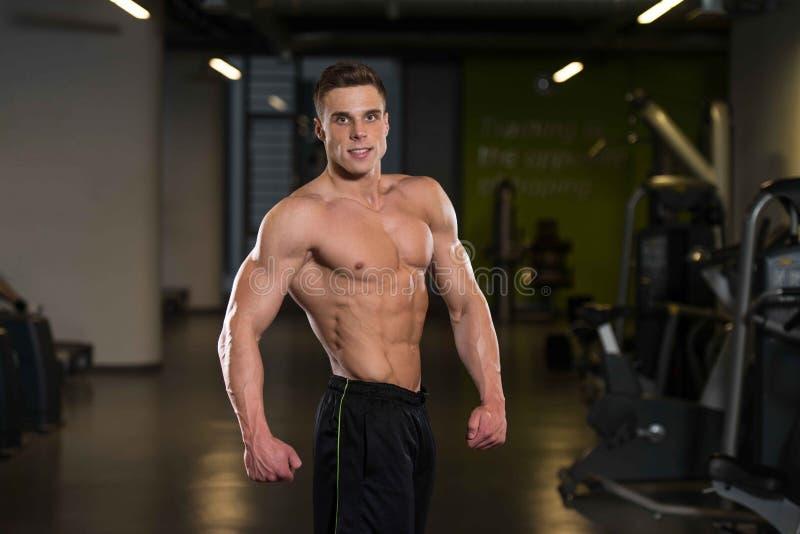 Homem no Gym que mostra seu corpo bem treinado foto de stock royalty free