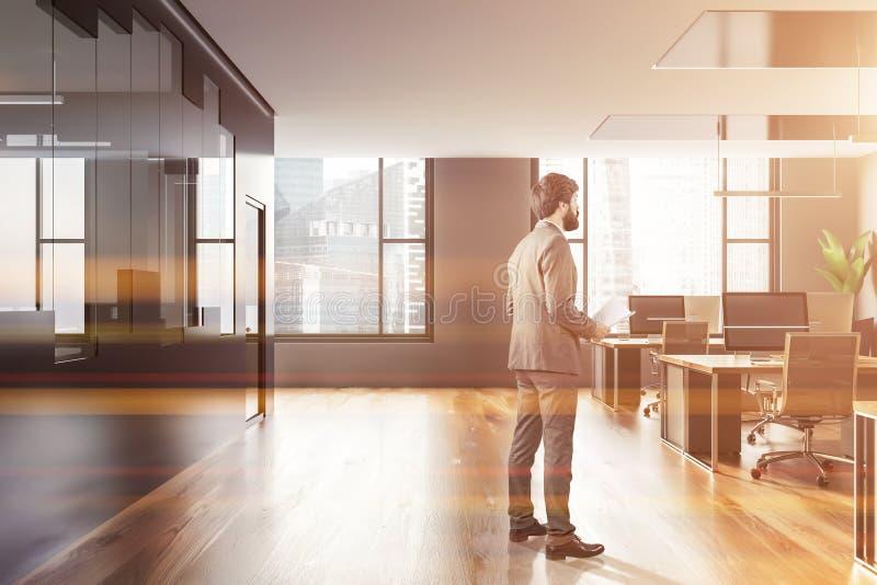 Homem no interior cinzento e de vidro do escritório do espaço aberto fotografia de stock royalty free
