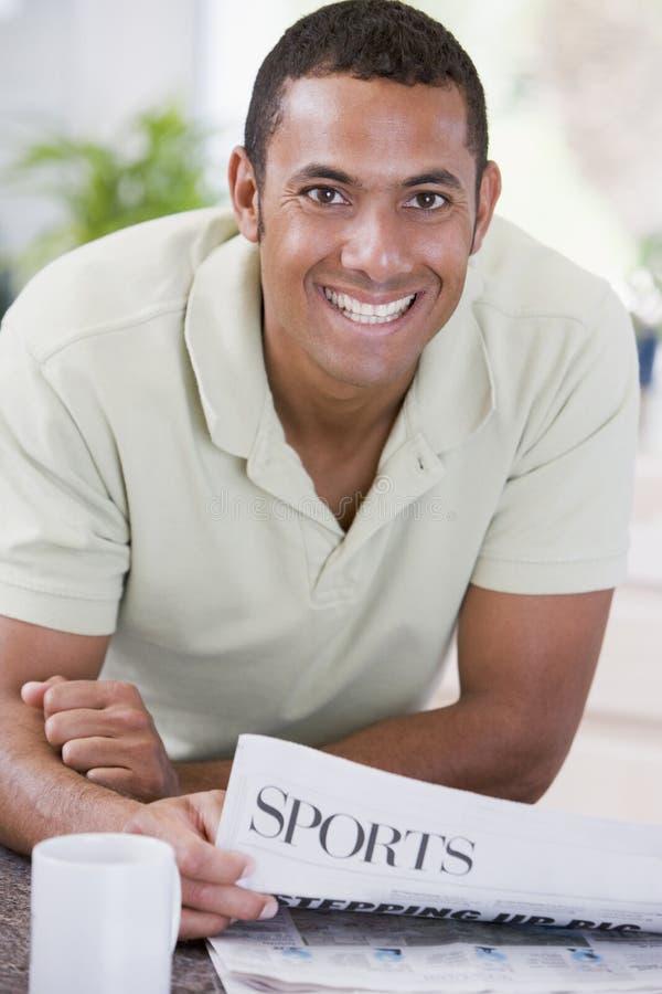 Homem no jornal e no sorriso da leitura da cozinha imagens de stock