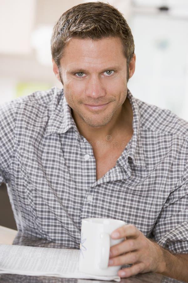 Homem no jornal e no sorriso da leitura da cozinha imagem de stock