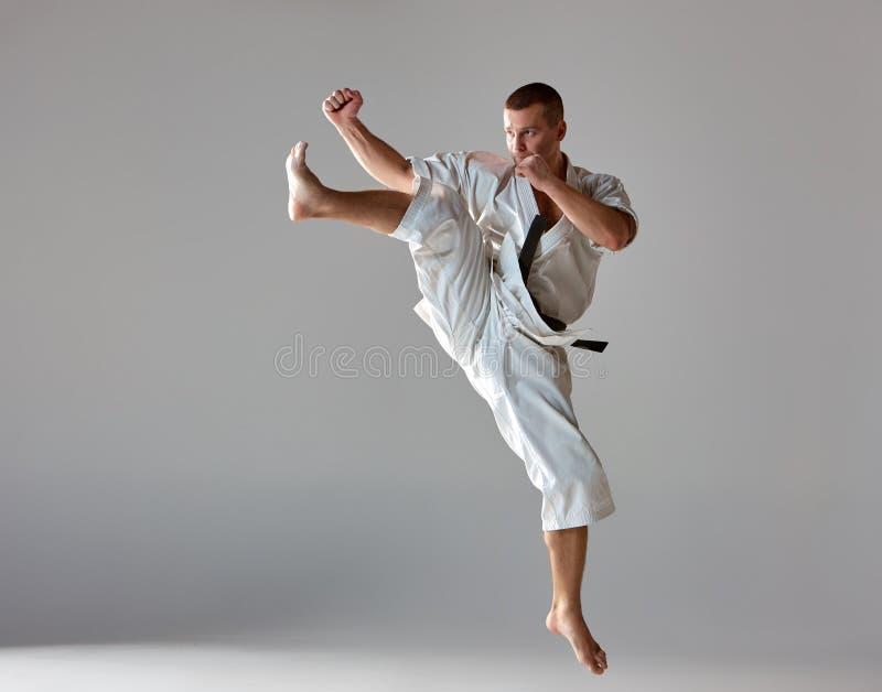 Homem no karaté branco do treinamento do quimono imagem de stock