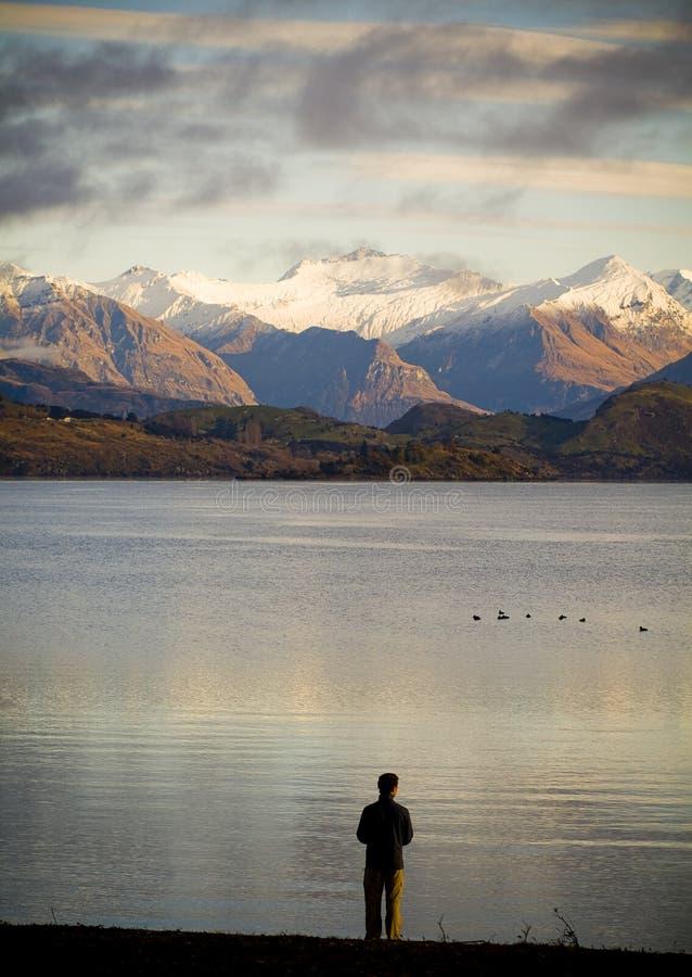 Homem no lago no alvorecer imagens de stock