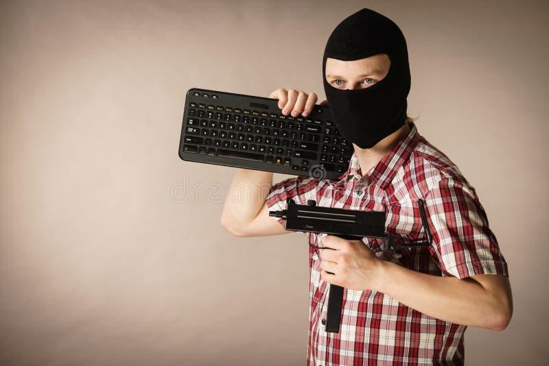Homem no passa-montanhas que guarda o teclado e a arma fotos de stock
