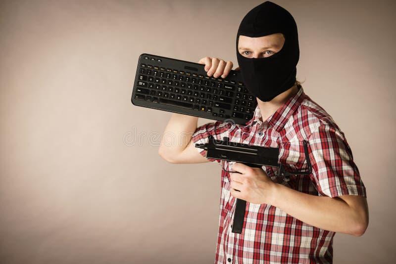 Homem no passa-montanhas que guarda o teclado e a arma fotos de stock royalty free