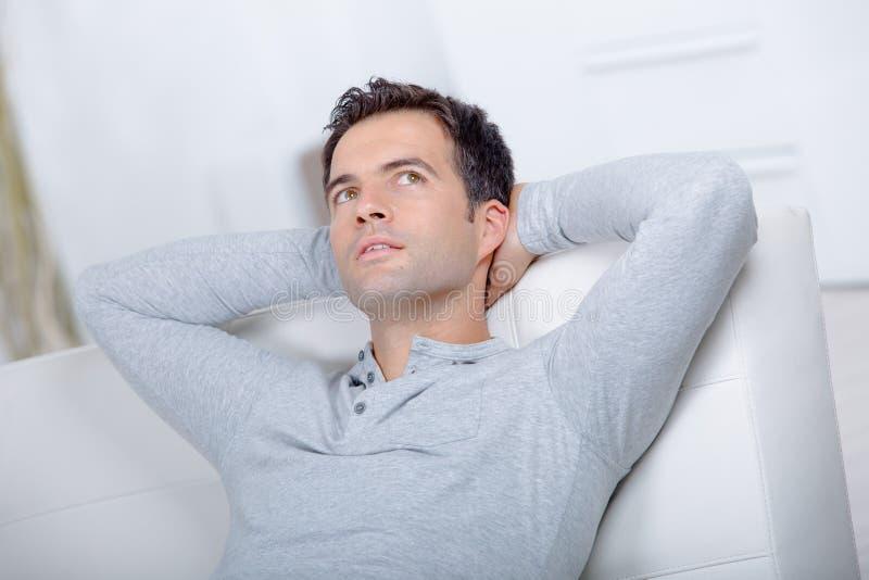 Homem no pensamento do sofá foto de stock