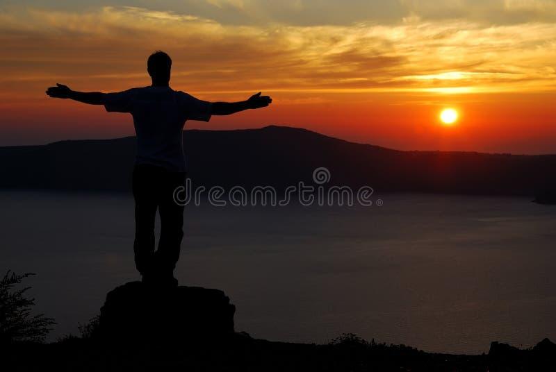 Homem no por do sol de Santorini sobre o litoral fotografia de stock royalty free