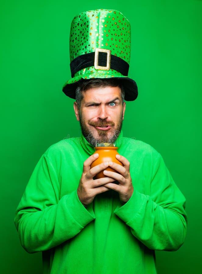 Homem no potenciômetro da posse do chapéu do partido do duende do dia de St Patrick de ouro no fundo verde Conceito feliz do dia  imagens de stock royalty free