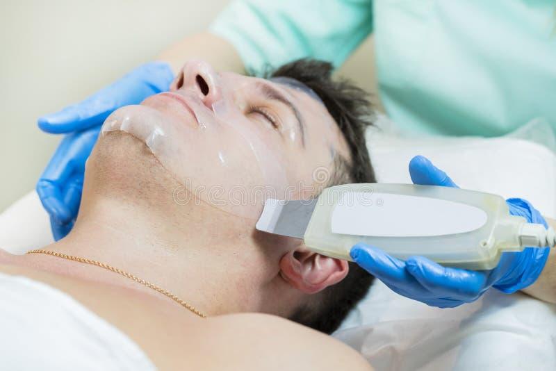 Homem no procedimento do cosmético da máscara imagens de stock royalty free
