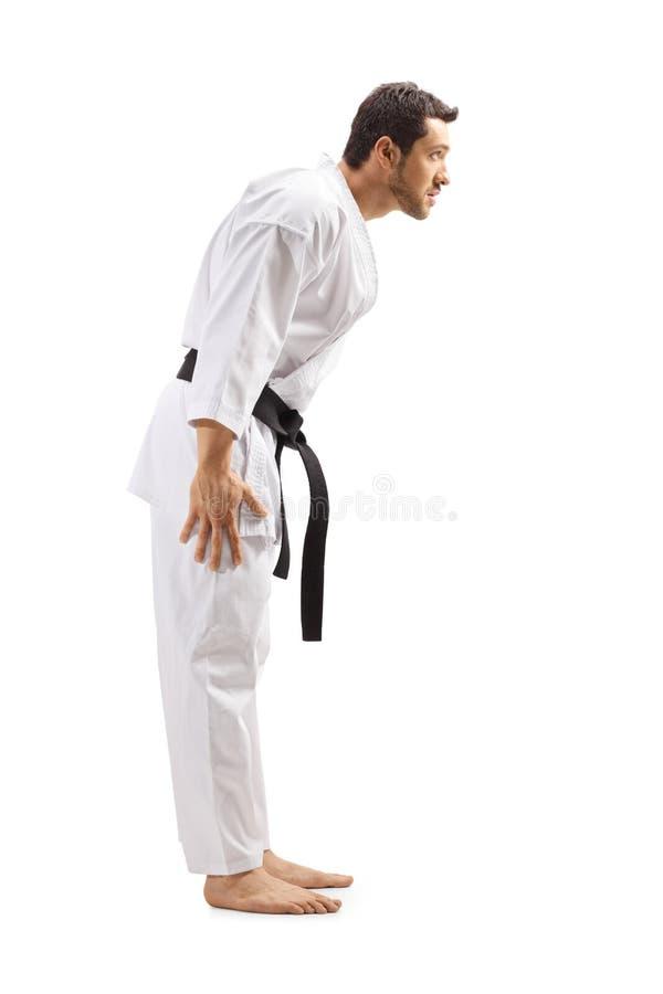 Homem no quimono do karaté com cinturão negro que ducking sua cabeça foto de stock royalty free