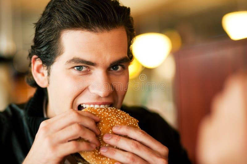 Homem no restaurante que come o Hamburger fotografia de stock royalty free