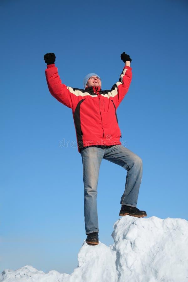 Homem no revestimento vermelho no monte da neve imagem de stock