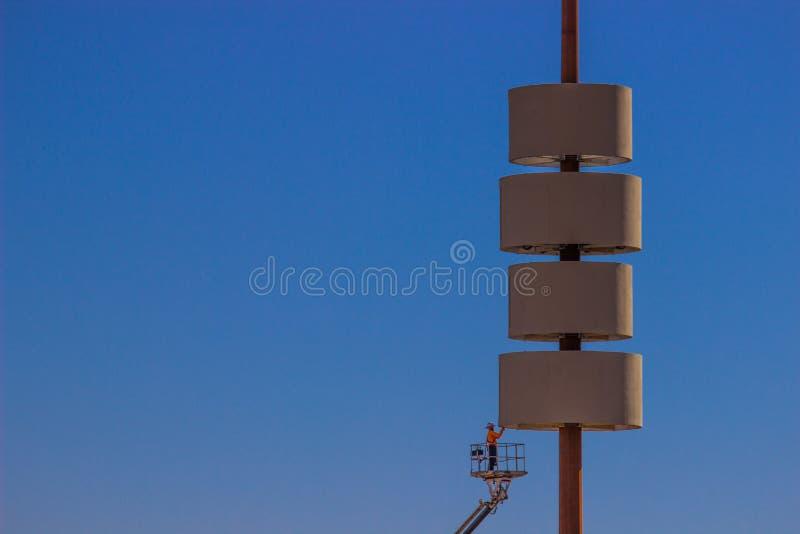 Homem no sinal exterior de Cherry Picker Lift Working On imagem de stock
