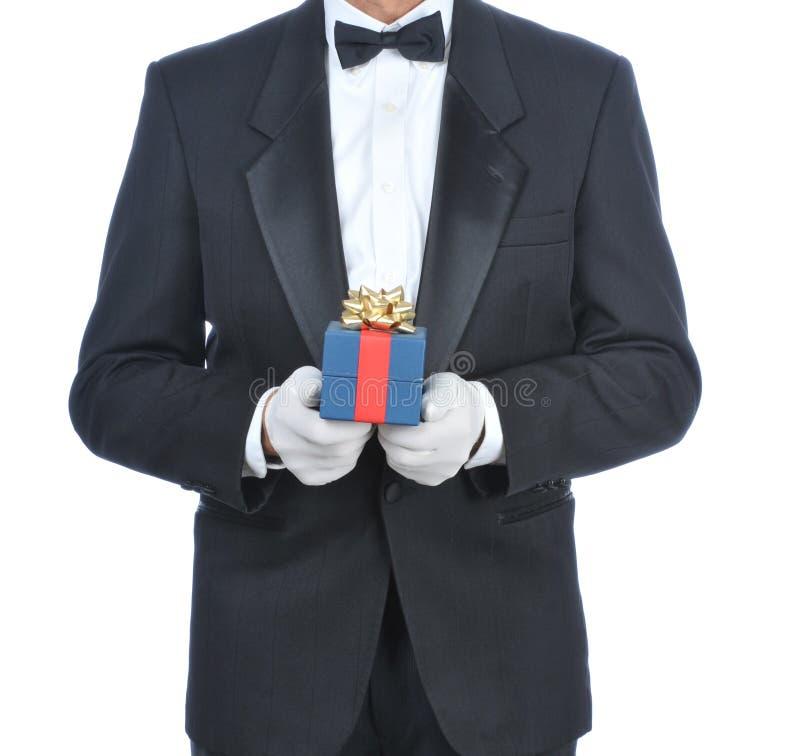 Homem no smoking com presente fotografia de stock royalty free
