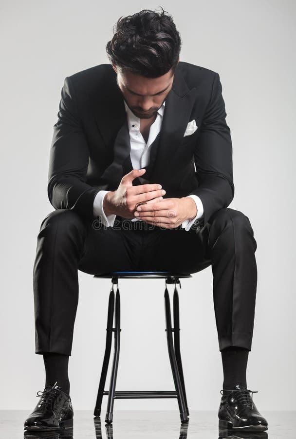 Homem no smoking que olha para baixo ao se sentar em um tamborete, fotos de stock