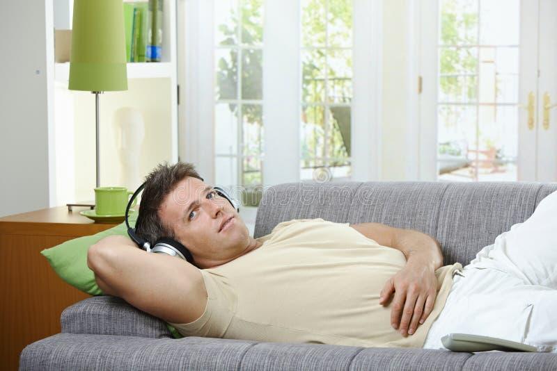 Download Homem No Sofá Que Escuta O Sorriso Da Música Imagem de Stock - Imagem de cheerful, apreciar: 12801301