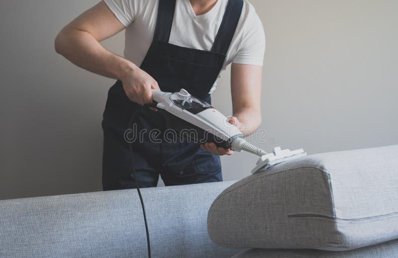 Homem no sofá uniforme da limpeza foto de stock royalty free