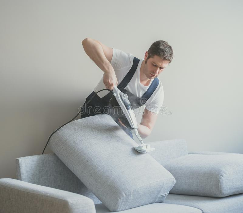 Homem no sofá uniforme da limpeza fotografia de stock