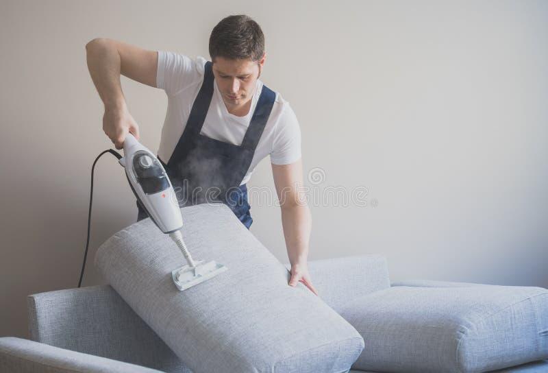 Homem no sofá uniforme da limpeza imagens de stock royalty free