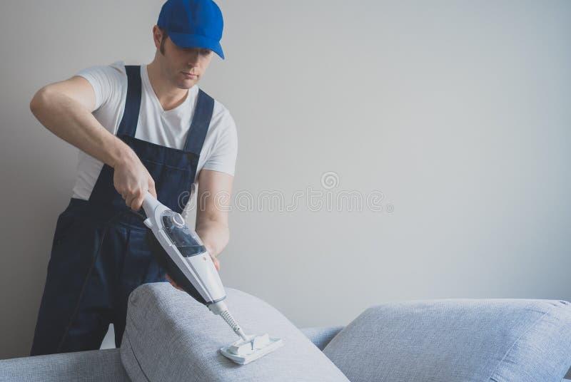Homem no sofá uniforme da limpeza imagem de stock royalty free