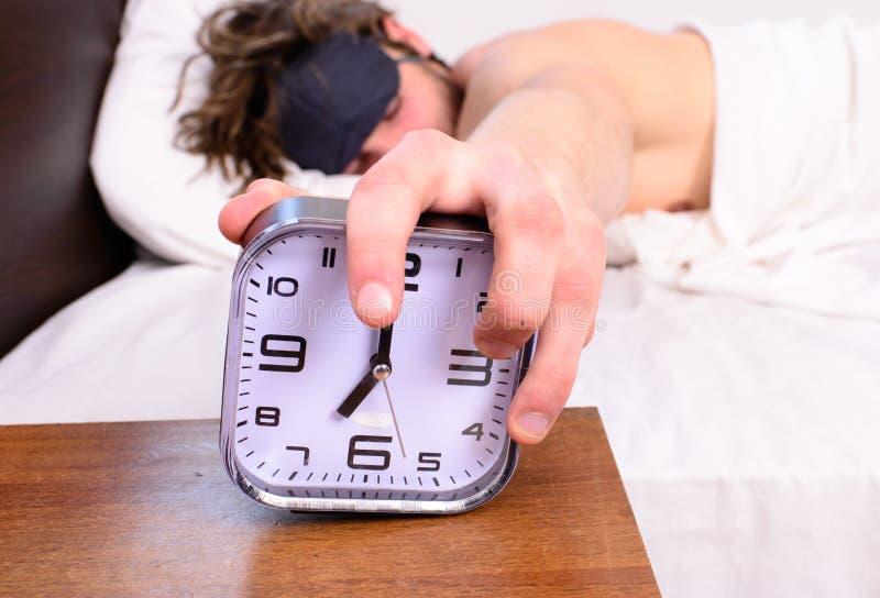 Homem no sono da máscara de olho melhor Despertador no fundo farpado não barbeado sonolento da máscara de olho do sono da cara do fotografia de stock