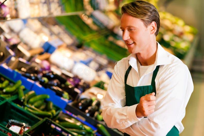 Homem no supermercado como o assistente de loja imagem de stock royalty free