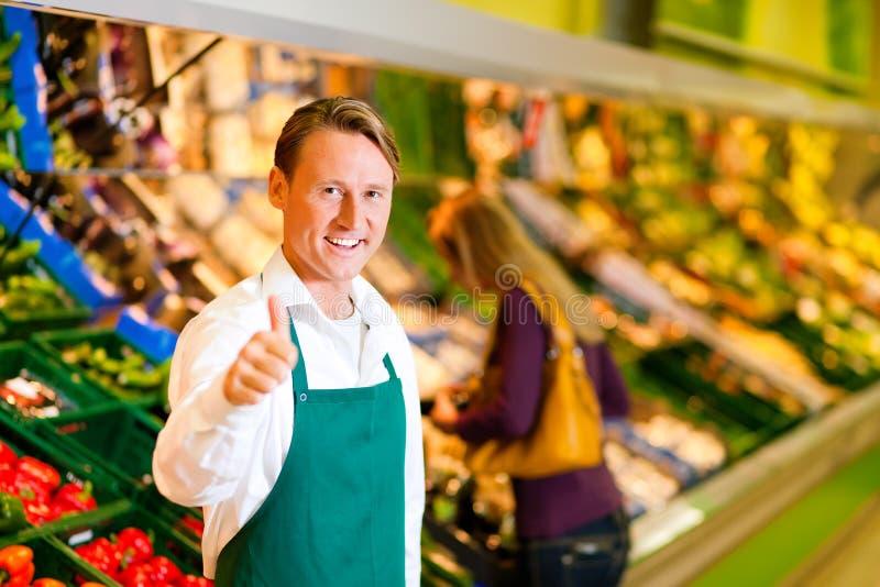 Homem no supermercado como o assistente de loja foto de stock