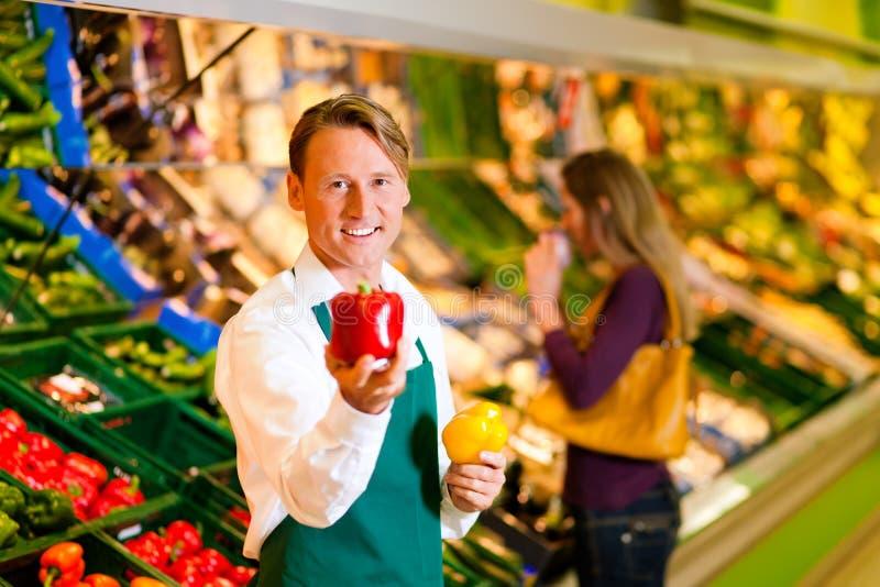Homem no supermercado como o assistente de loja fotos de stock