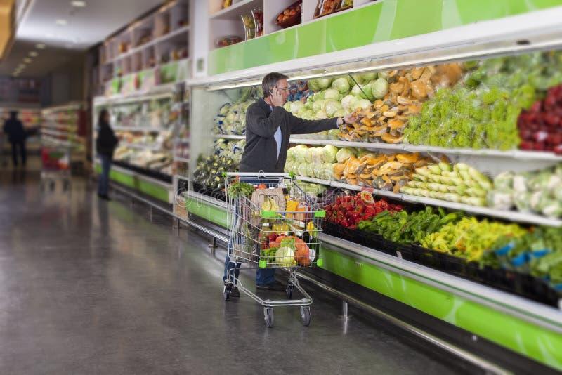 Homem no supermercado e no telemóvel fotografia de stock royalty free