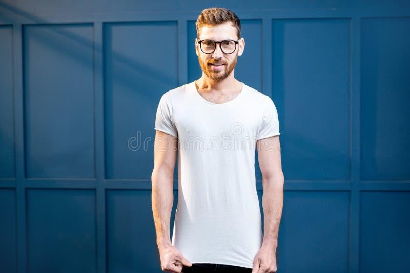 Homem no t-shirt branco no fundo azul imagens de stock royalty free