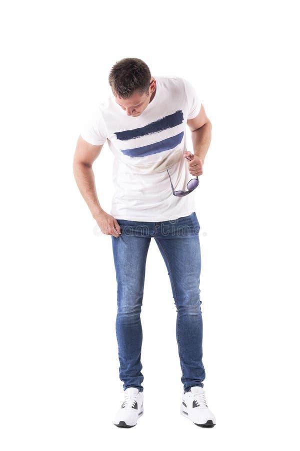 Homem no t-shirt branco que guarda os óculos de sol que olham abaixo de ajustar calças de brim fotografia de stock royalty free