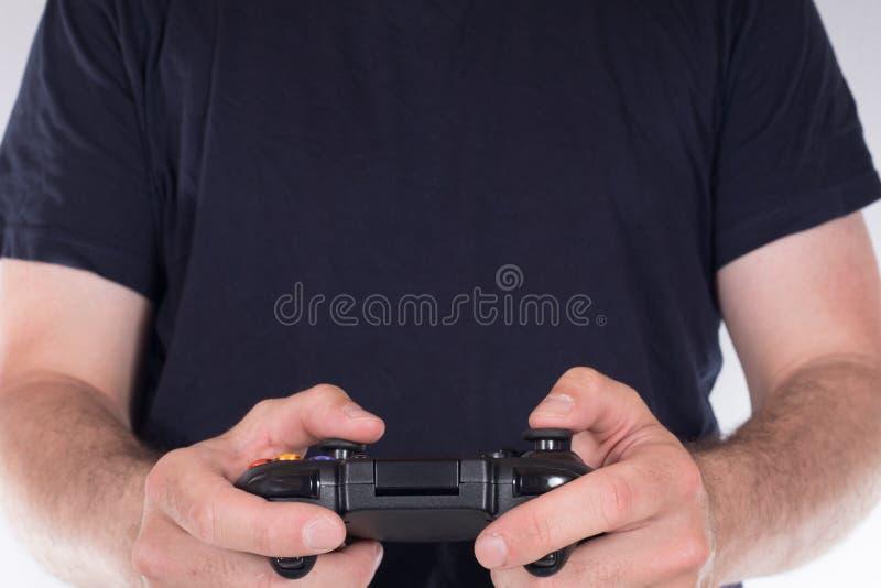 Homem no t-shirt preto que joga jogos de vídeo imagem de stock royalty free