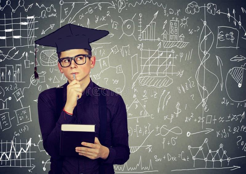 Homem no tampão da graduação com livro que pensa sobre a educação foto de stock