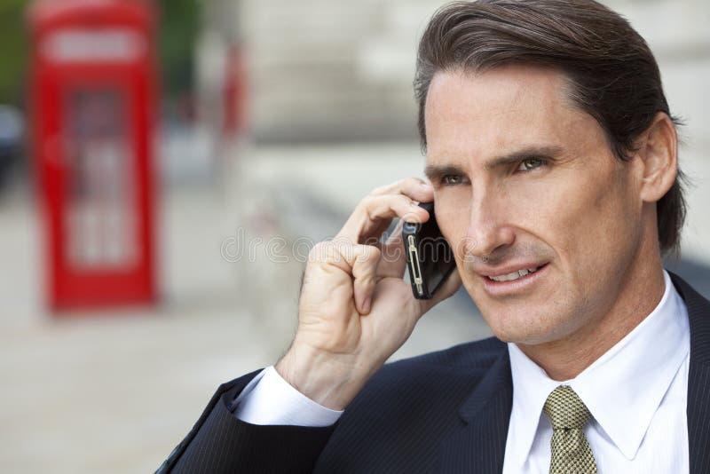 Homem no telefone de pilha com a caixa de telefone vermelha de Londres foto de stock royalty free