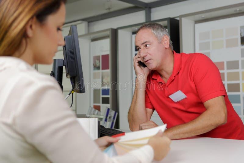 Homem no telefone que ajuda ao cliente no armazém fotografia de stock