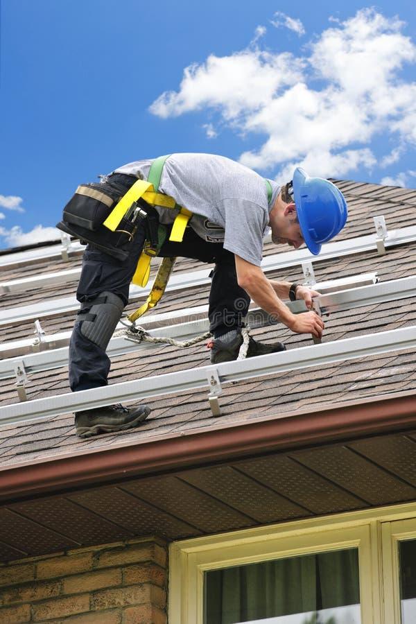 Homem no telhado que instala os trilhos para os painéis solares fotografia de stock