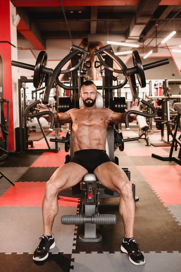 Homem no tema do esporte Desportista que dá certo no gym Halterofilista muscular que faz exercícios fotografia de stock