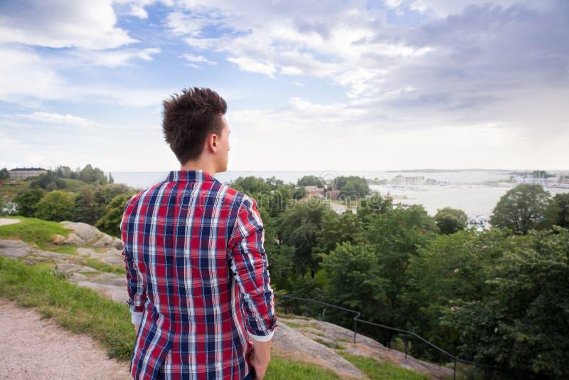 Homem no terno à moda que olha para a frente ao horizonte de mar imagem de stock