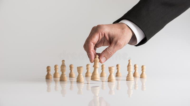 Homem no terno de negócio que joga a xadrez que move o liftin da parte da rainha fotografia de stock