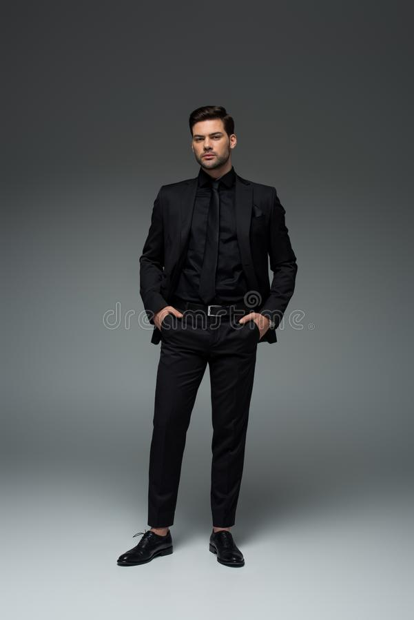 Homem no terno preto à moda que está com os dedos em uns bolsos imagem de stock royalty free