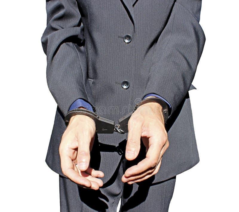 Homem no terno preto nas algemas em suas mãos isoladas fotografia de stock royalty free