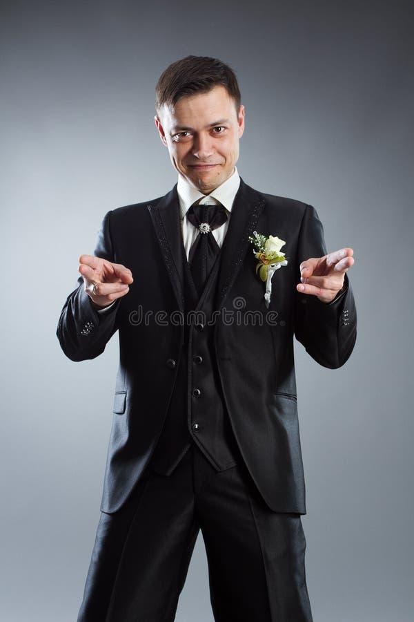 Homem no terno preto que aponta os dedos na parte dianteira imagem de stock royalty free