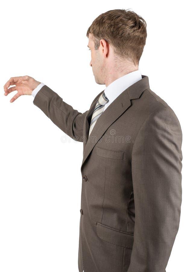 Homem no terno que alcança para algo de imagens de stock